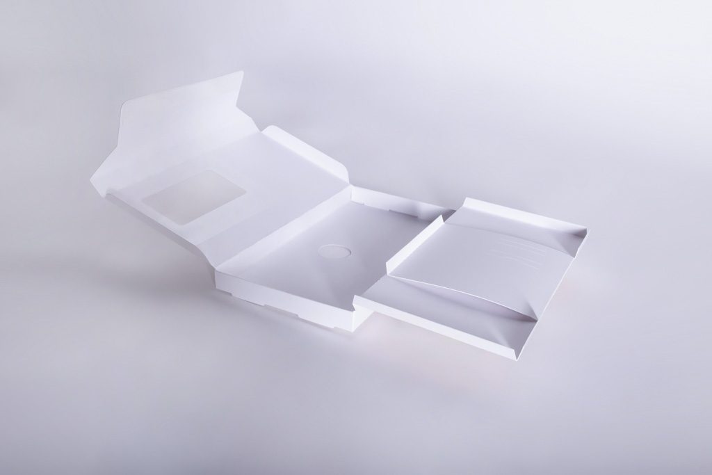 Eine Versandschachtel mit Adressfenster, Aufreißperforation und Inneneinrichtung. - Mugler Masterpack GmbH